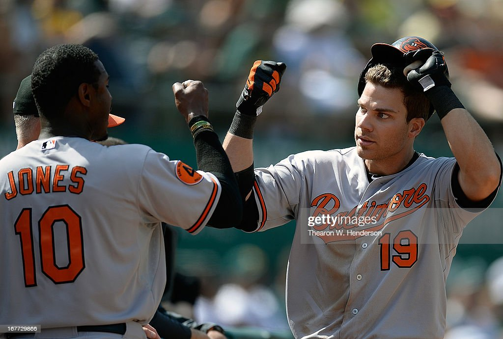 Chris Davis #19 of the Baltimore Orioles is congratulates by Adam Jones after Davis hit a solo home run the that put the Orioles ahead of the Oakland Athletics 7-6 in the eighth inning at O.co Coliseum on April 28, 2013 in Oakland, California.