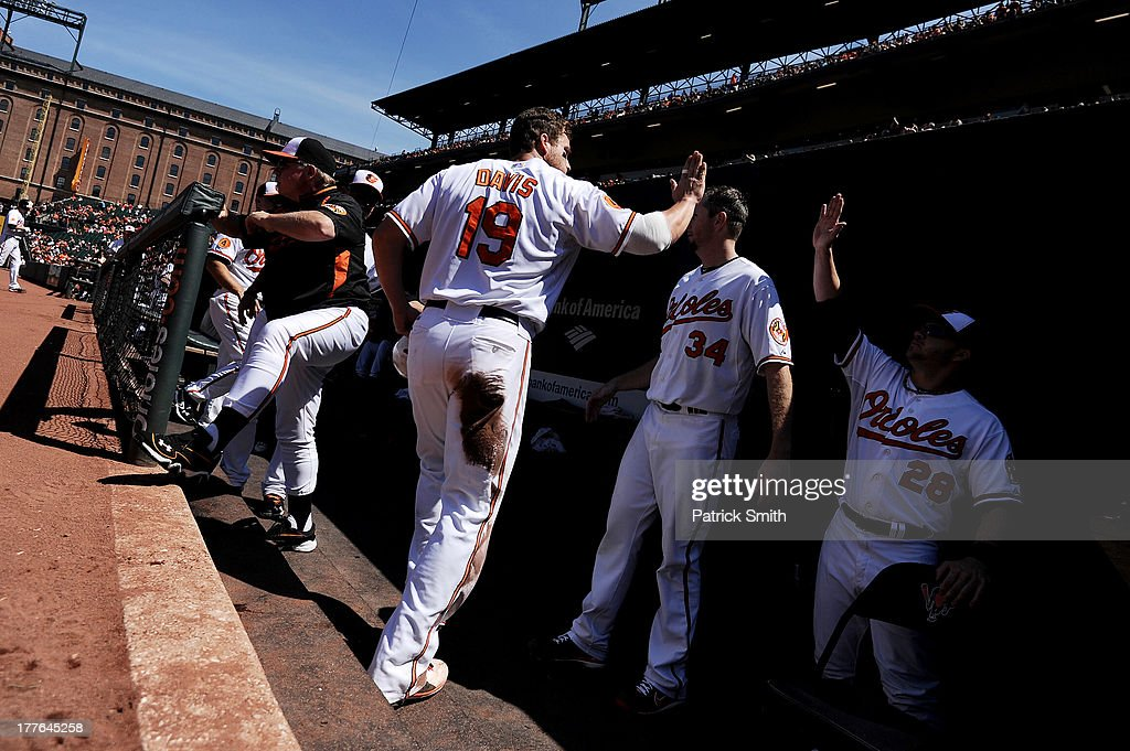 Chris Davis #19 of the Baltimore Orioles is greeted in the dugout after scoring off of a Matt Wieters (not pictured) sacrifice fly against the Oakland Athletics in the first inning at Oriole Park at Camden Yards on August 25, 2013 in Baltimore, Maryland.