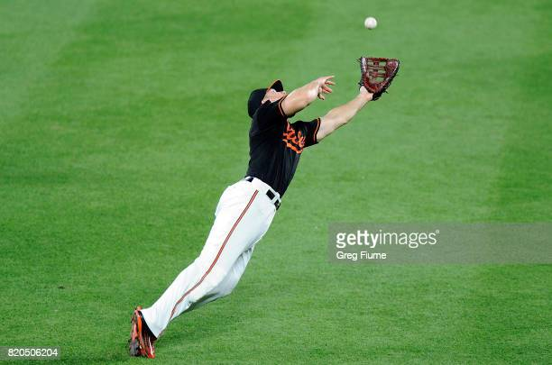 Chris Davis of the Baltimore Orioles makes a diving catch on a ball hit by Carlos Beltran of the Houston Astros in the sixth inning at Oriole Park at...
