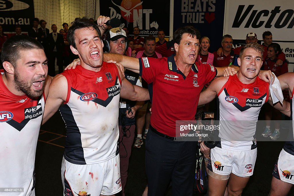 Chris Dawes (L) Cameron Pedersen, coach Paul Roos and Dean Kent (R) of the Demons celebrate their win during the round four AFL match between the Carlton Blues and the Melbourne Demons at Melbourne Cricket Ground on April 12, 2014 in Melbourne, Australia.