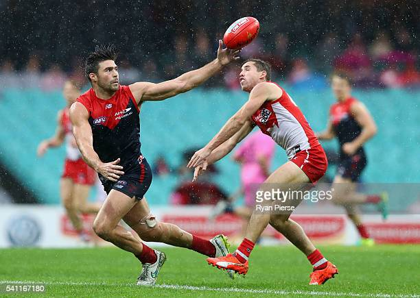 Chris Dawes of the Demons competes for the ball against Jake Lloyd of the Swans during the round 13 AFL match between the Sydney Swans and the...