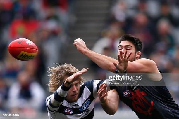 Chris Dawes of the Demons handballs as Cameron Guthrie of the Cats attempts to smother the ball during the round 17 AFL match between the Melbourne...