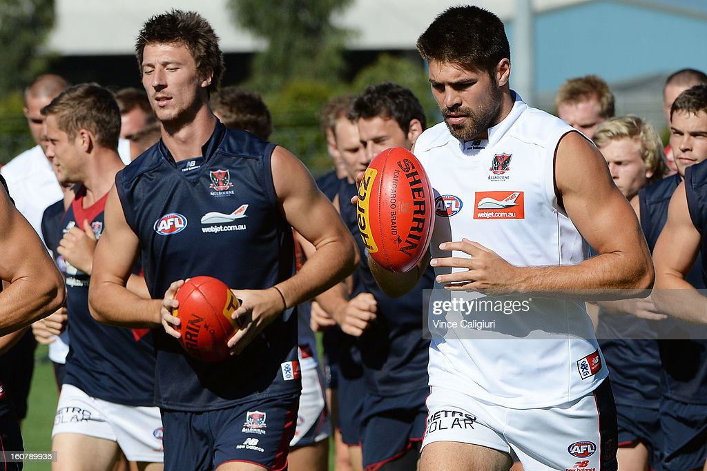 Chris Dawes (R) runs laps with teammates during a Melbourne Demons AFL training session at Gosch's Paddock on February 6, 2013 in Melbourne, Australia.