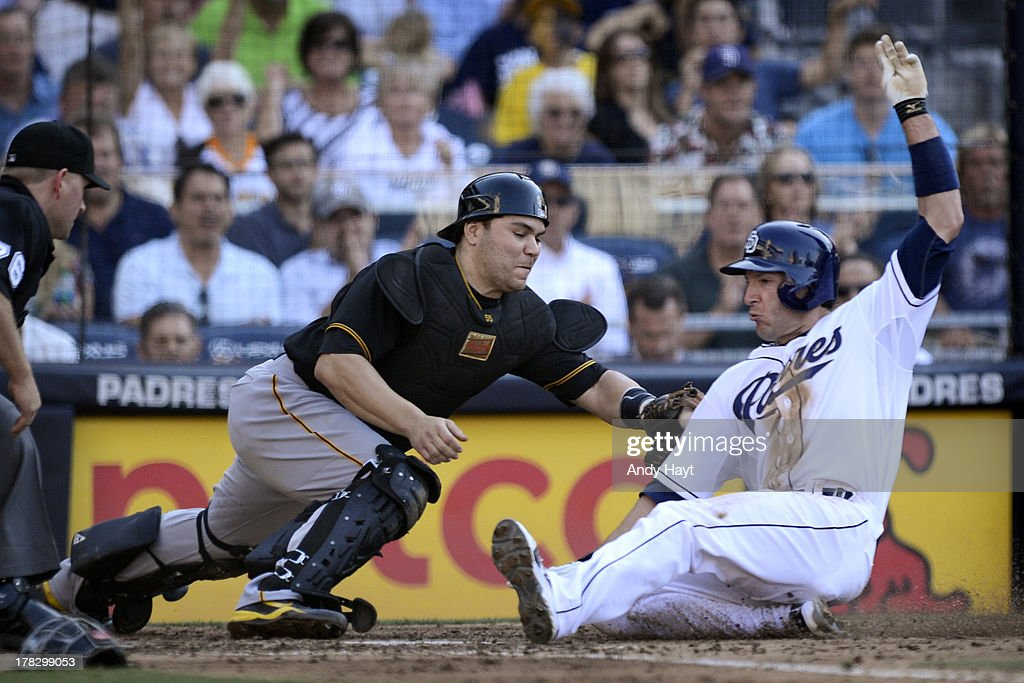Chris Denorfia #13 of the San Diego Padres is safe at home against as Russell Martin #55 of the Pittsburgh Pirates tries to apply the tag at Petco Park on August 21, 2013 in San Diego, California.
