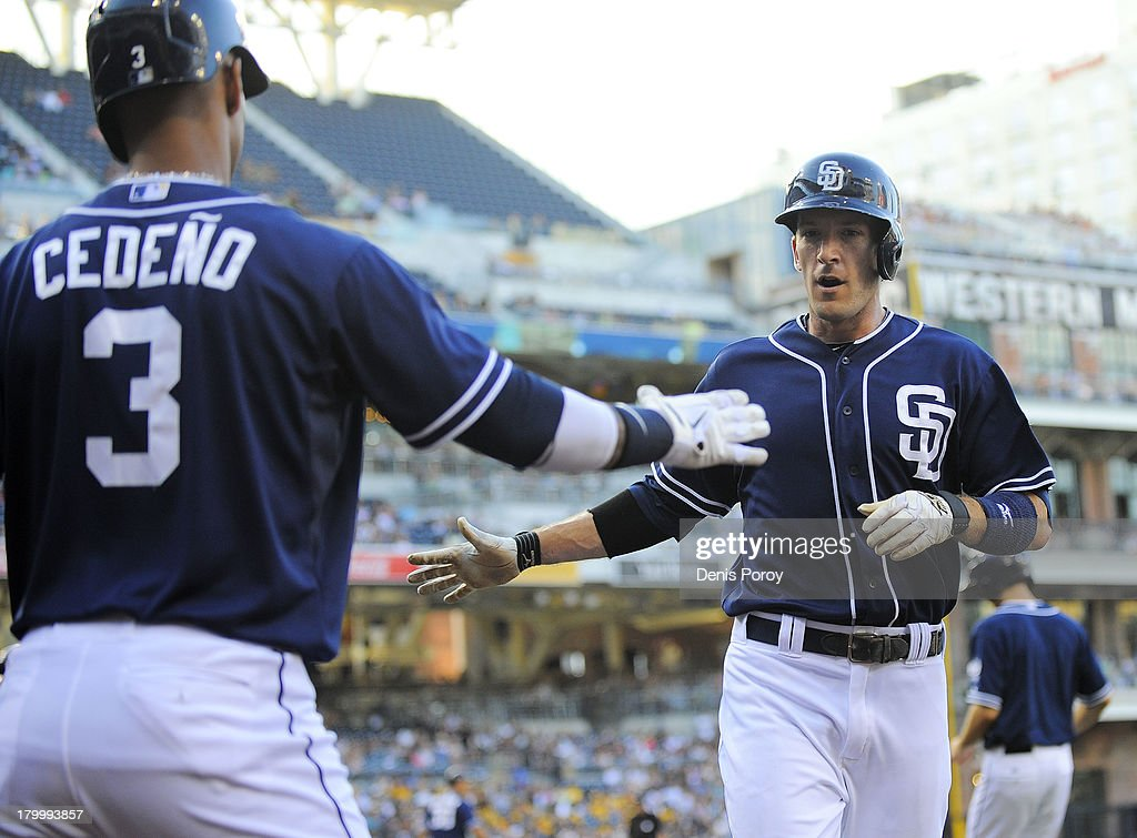 Chris Denorfia of the San Diego Padres right is congratulated by Ronny Cedeno after scoring during the first inning of a baseball game against the...