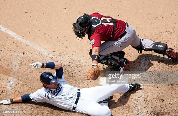 Chris Denorfia of the San Diego Padres slides into homeplate scoring a run in the 7th inning of the game beating the tag of catcher Chris Snyder of...