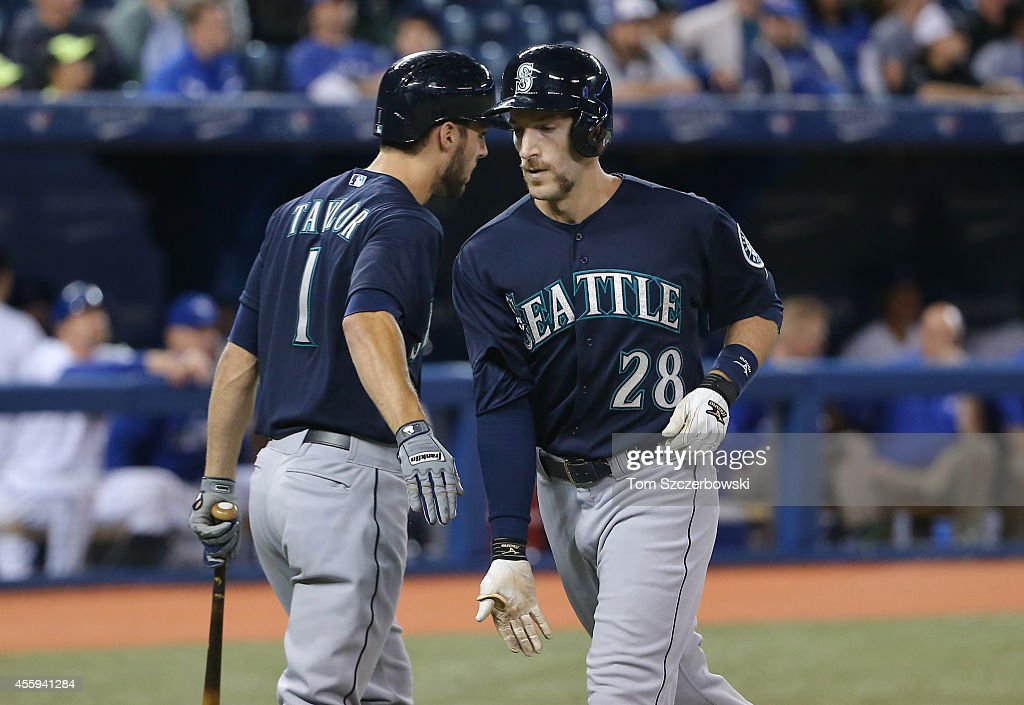 Chris Denorfia #65 of the Seattle Mariners is congratulated by Chris Taylor #1 after hitting a solo home run in the ninth inning during MLB game action against the Toronto Blue Jays on September 22, 2014 at Rogers Centre in Toronto, Ontario, Canada.