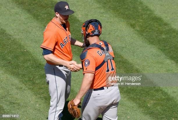 Chris Devenski and Evan Gattis of the Houston Astros celebrates defeating the Oakland Athletics 129 at Oakland Alameda Coliseum on June 22 2017 in...