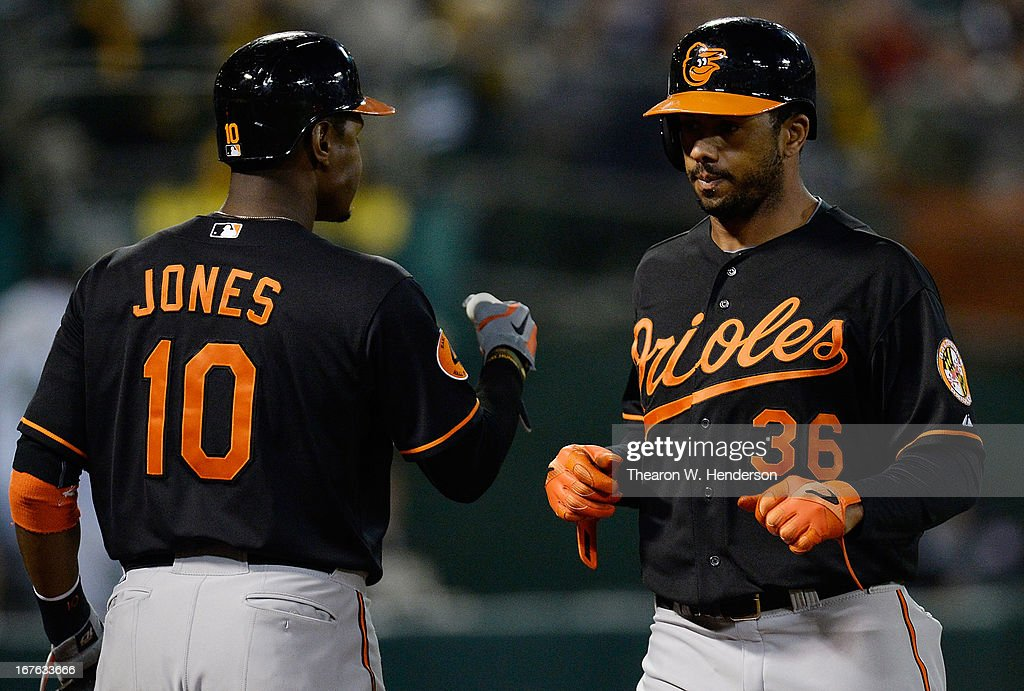 Chris Dickerson #36 of the Baltimore Orioles is congratulated by Adam Jones #10 after Dickerson scored on a sacrifice fly from Nick Markakis (not pictured) against the Oakland Athletics in the ninth inning at O.co Coliseum on April 26, 2013 in Oakland, California. The Orioles won the game 3-0.