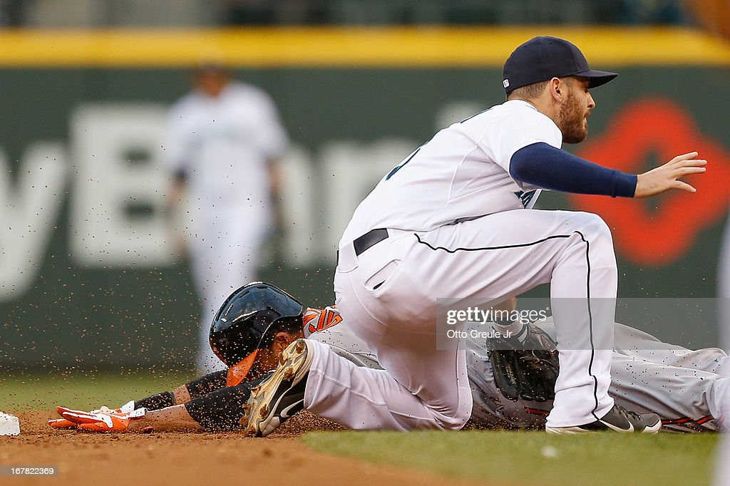 Chris Dickerson #36 of the Baltimore Orioles is tagged out on a steal attempt by <a gi-track='captionPersonalityLinkClicked' href=/galleries/search?phrase=Dustin+Ackley&family=editorial&specificpeople=4352278 ng-click='$event.stopPropagation()'>Dustin Ackley</a> #13 of the Seattle Mariners in the second inning at Safeco Field on April 30, 2013 in Seattle, Washington.