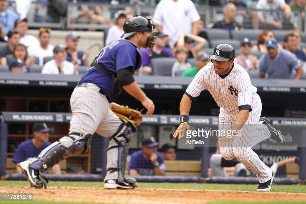 Chris Dickerson of the New York Yankees scores the go ahead run as Chris Iannetta of the Colorado Rockies waits for the ball during their game on...