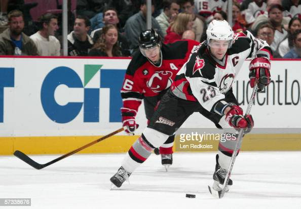 Chris Drury of the Buffalo Sabres skates with the puck past Patrik Elias of the New Jersey Devils during the game at Continental Airlines Arena on...