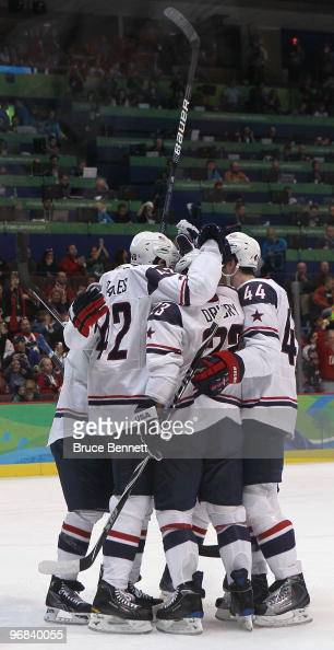 Chris Drury of The United States celebrates with teammates after scoring his team's second goal during the ice hockey men's preliminary game between...