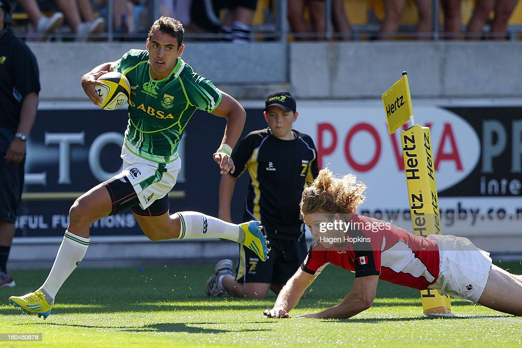 Chris Dry of South Africa scores a try after beating the tackle of Conor Trainor of Canada in the pool C game between South Africa and Canada during the 2013 Wellington Sevens at Westpac Stadium on February 1, 2013 in Wellington, New Zealand.