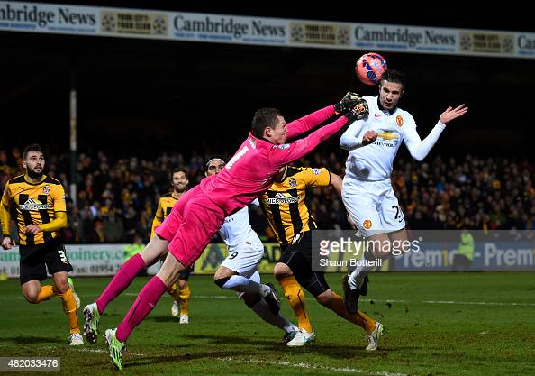 Chris Dunn of Cambridge United makes contact with Robin van Persie of Manchester United as he punches the ball clear during the FA Cup Fourth Round...