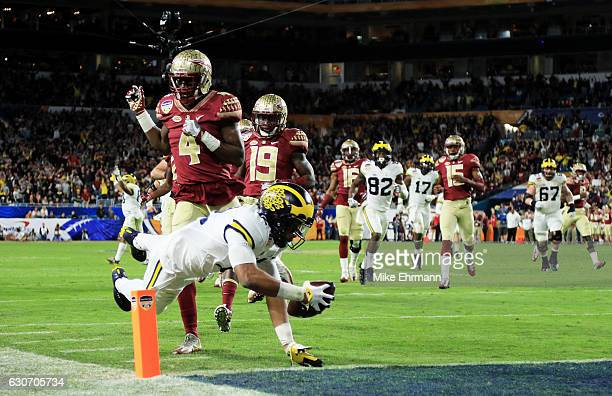 Chris Evans of the Michigan Wolverines runs for a 30yard touchdown in the fourth quarter as Tarvarus McFadden of the Florida State Seminoles defends...