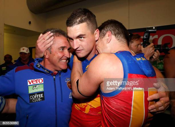 Chris Fagan Senior Coach of the Lions celebrates with Tom Rockliff and Dayne Zorko of the Lions during the 2017 AFL round 15 match between the...