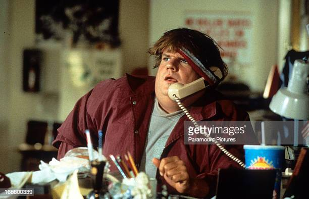 Chris Farley holding a phone receiver underneath his headband to keep it propped up to his ear in a scene from the film 'Black Sheep' 1996