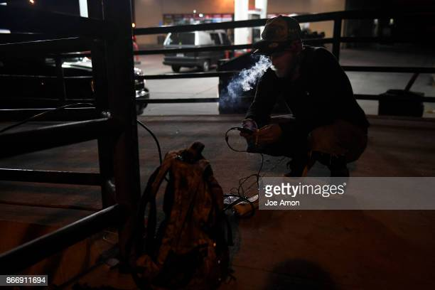 Chris Farrell 32 from Ohio using a plug he found near a gas station to power up phones for him and his wife The couple have been in Denver for 6 yrs...