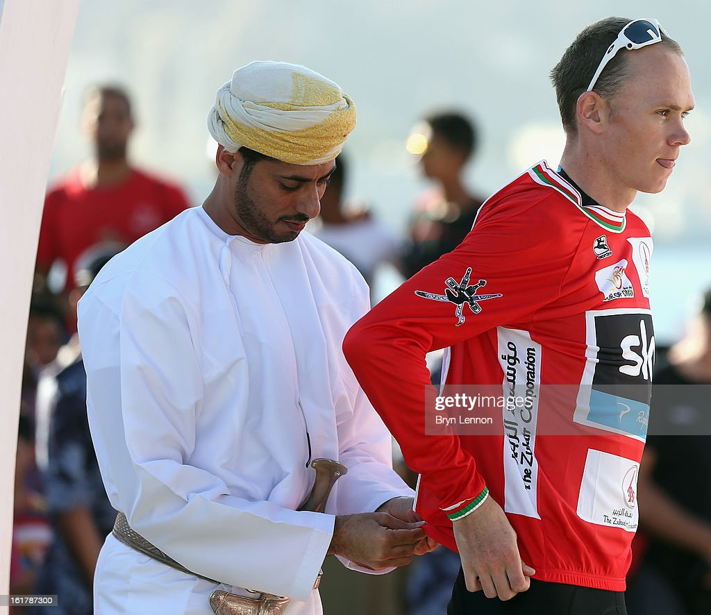 Chris Froome of Great Britain and SKY Procycling puts on the red jersey after winning the 2013 Tour of Oman from Hawit Nagam Park to the Matrah Corniche on February 16, 2013 in Matrah, Oman.