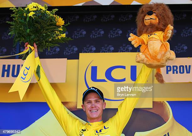 Chris Froome of Great Britain and Team Sky celebrates as he is awarded the yellow jersey on the podium after stage three of the 2015 Tour de France a...
