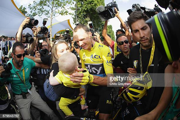 Chris Froome of Great Britain and Team Sky celebrates victory with his family as he is surrounded by the media during stage twenty one of the 2016 Le...