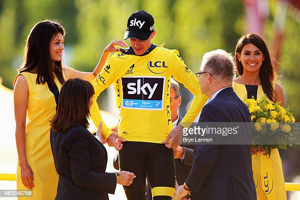 Chris Froome of Great Britain and Team Sky receives the yellow jersey on the podium after his overall win following the twenty first stage of the...