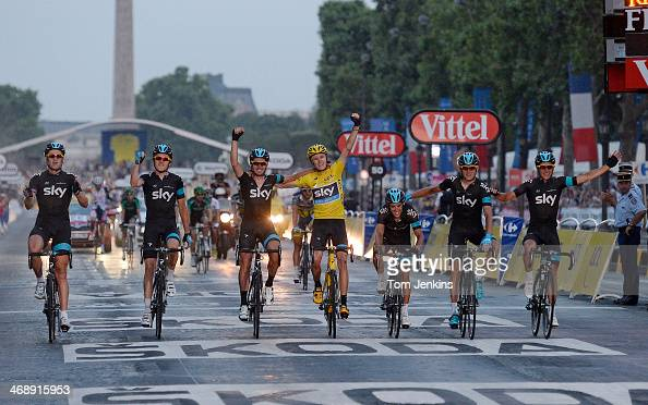 Chris Froome of Great Britain in the yellow jersey celebrates overall victory as he crosses the finish line with his Team Sky teammates during stage...