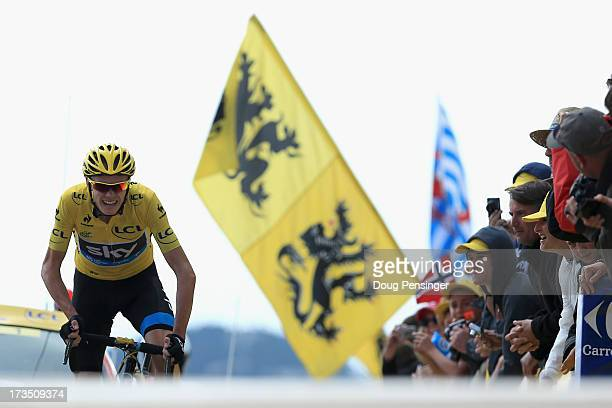 Chris Froome of Great Britain riding for Sky Procycling wearing the overall race leader's yellow jersey charges toward the finish line as he claims...