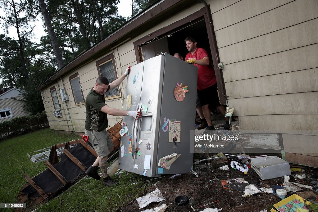 Chris Gaspard (R) and Derek Pelt (L) help remove a refrigerator and other ruined items from their friend Bryan Parson's home following flooding in the wake of Hurricane Harvey September 1, 2017 in Dickinson, Texas. Dickinson was hit by Hurricane Harvey extremely hard with major flooding in many areas of the city and residents there are beginning the long process of recovery from the storm.