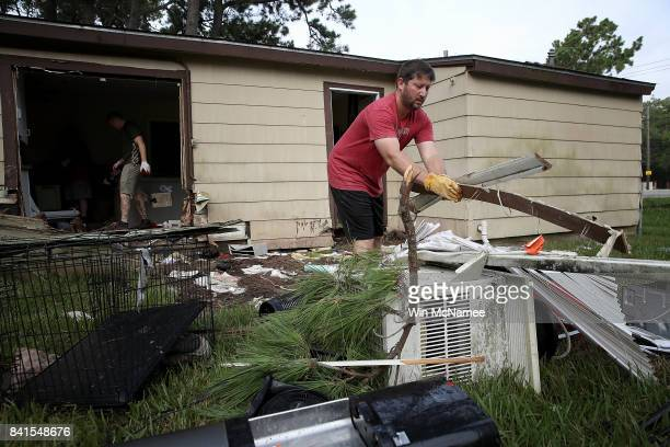 Chris Gaspard helps remove ruined items from his friend Bryan Parson's home brought on by flooding in the wake of Hurricane Harvey September 1 2017...