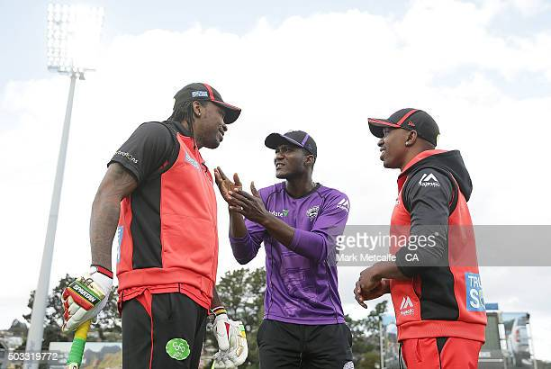 Chris Gayle and Dwayne Bravo of the Renegades and Darren Sammy of the Hurricanes talk on the field before the Big Bash League match between the...