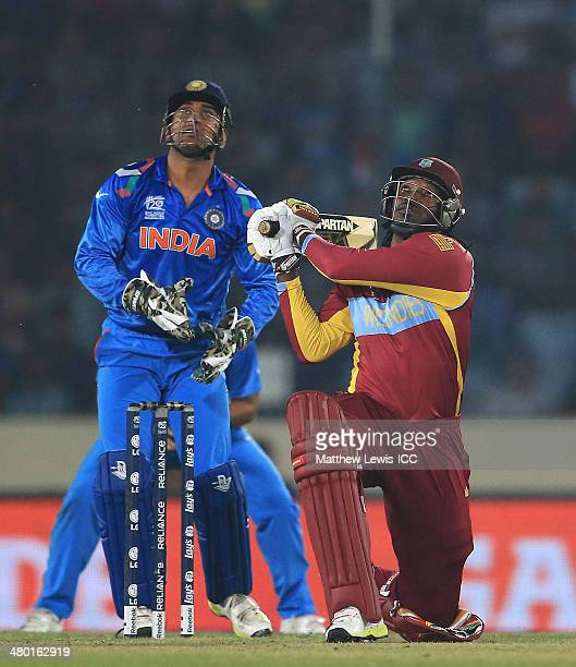 Chris Gayle of the West Indies hits the ball towards the boundary as MS Dhoni of India looks on during the ICC World Twenty20 Bangladesh 2014 match...
