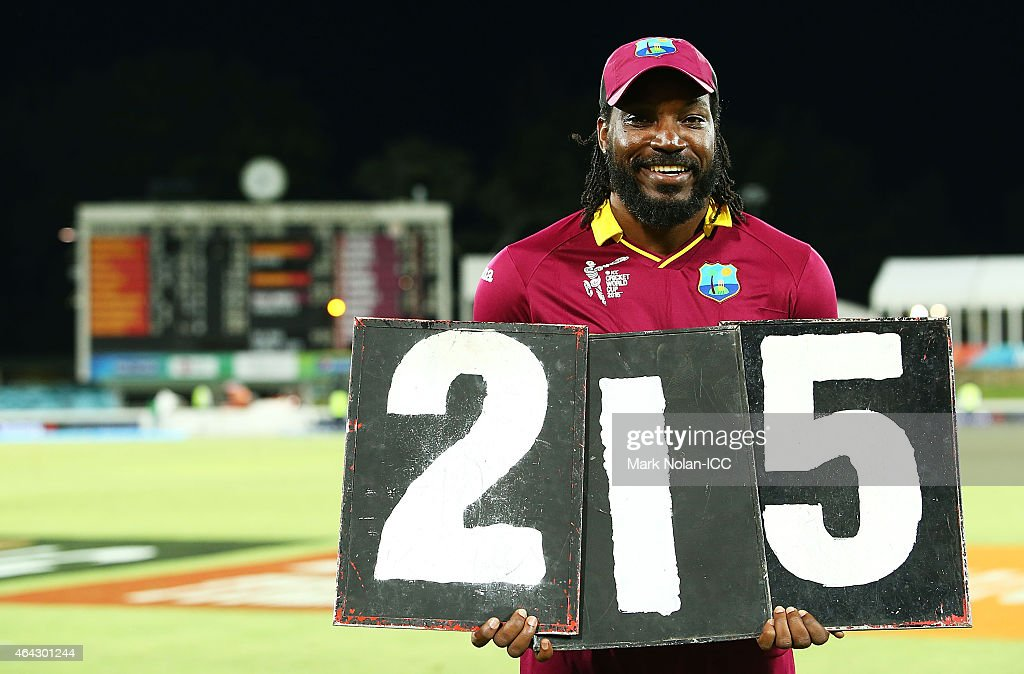 Chris Gayle of the West Indies poses with the scored board figures that represent his record breaking innings o 215 during the 2015 ICC Cricket World Cup match between the West Indies and Zimbabwe at Manuka Oval on February 24, 2015 in Canberra, Australia.