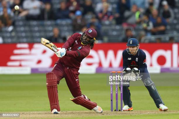 Chris Gayle of West Indies hits a straight six off the bowling of Moeen Ali as England wicketkeeper Jos Buttler looks on during the third Royal...