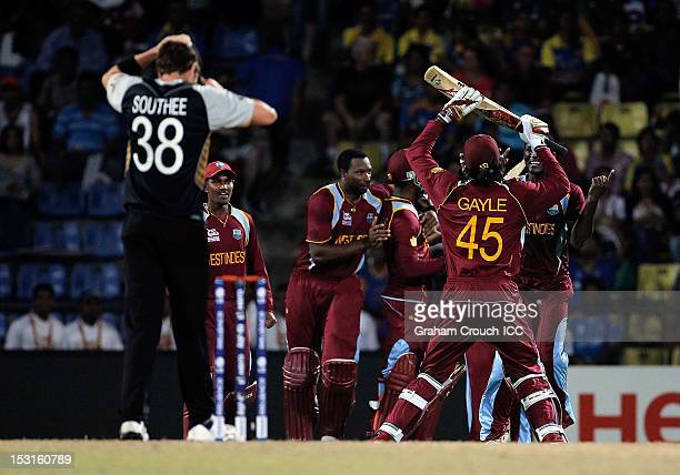 Chris Gayle of West Indies reacts with team mates after winning the Super Over with Tim Southee of New Zealand the bowler during the Super Eights...