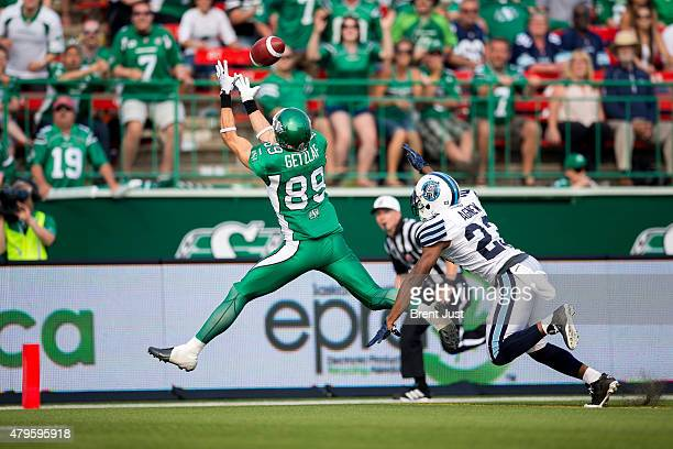 Chris Getzlaf of the Saskatchewan Roughriders catches a touchdown behind Vincent Agnew of the Toronto Argonauts in overtime in the game between the...