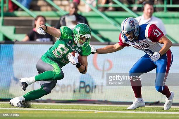 Chris Getzlaf of the Saskatchewan Roughriders makes a catch in front of Chip Cox of the Montreal Alouettes in a game between the Montreal Alouettes...