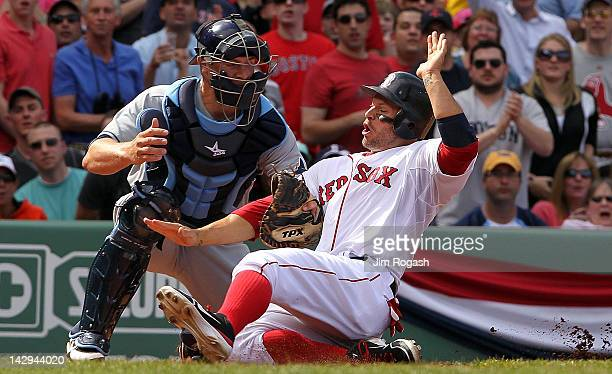 Chris Gimenez of the Tampa Bay Rays tags out Cody Ross of the Boston Red Sox at the plate in the fifth inning at Fenway Park April 15 2012 in Boston...
