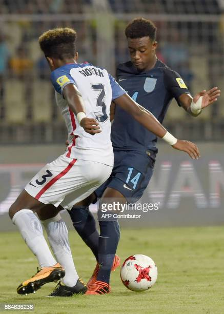 Chris Gloster of USA tackles Callum HudsonOdoi of England during the quarterfinal football match between USA and England in the FIFA U17 World Cup at...