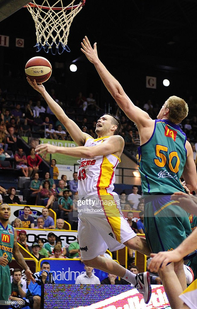 Chris Goulding of the Tigers makes a layup past Luke Nevill of the Crocodiles during the round ten NBL match between the Townsville Crocodiles and the Melbourne Tigers at Townsville Entertainment Centre on December 8, 2012 in Townsville, Australia.