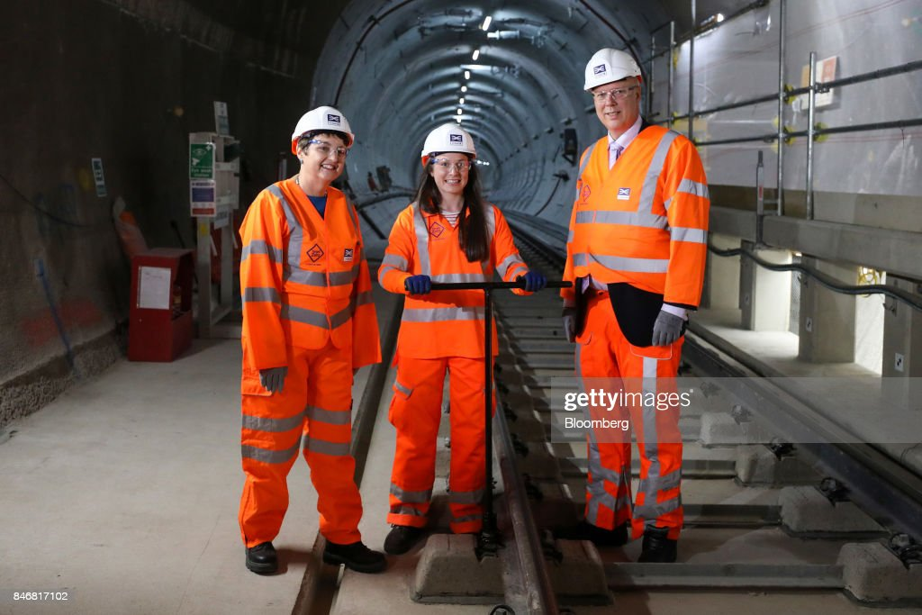 Chris Grayling, U.K. transport secretary, right, Val Shawcross, deputy London mayor for Transport, left, and Ellen McGuinness, a track engineer, pose for a photograph during an event in a tunnel near Whitechapel station to celebrate the completion of the permanent Crossrail Ltd. track on the Elizabeth line in London, U.K., on Thursday, Sept. 14, 2017. Crossrail, which will be known as the Elizabeth Line once its up and running, hasnt yet set fares, but transit agency Transport for London has indicated they will be significantly less than Heathrow Express with a charging structure more akin to the Tube. Photographer: Chris Ratcliffe/Bloomberg via Getty Images
