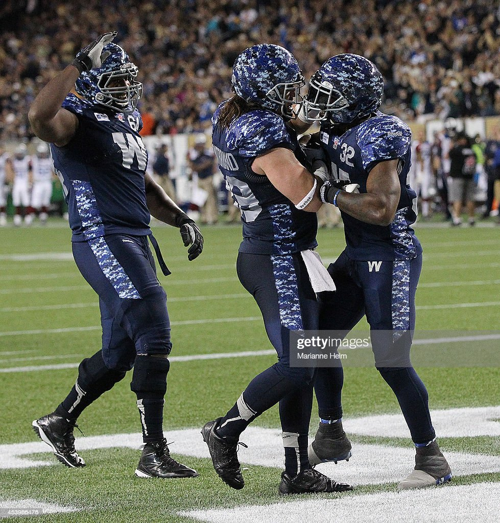 Chris Greaves #64 and Michel-Pierre Pontbriand #39 of the Winnipeg Blue Bombers congratulate teammate Nic Grigsby #32 for his touchdown in fourth quarter action in a CFL game against the Montreal Alouettes at Investors Group Field on August 22, 2014 in Winnipeg, Manitoba, Canada.