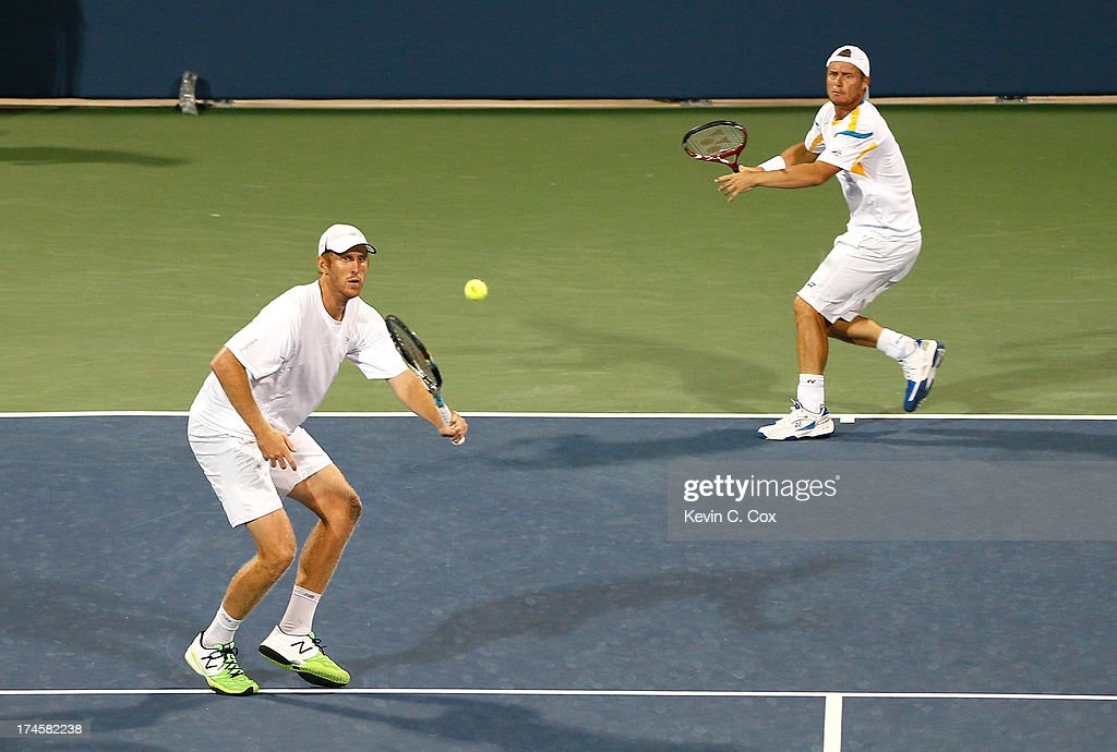 Chris Guccione and <a gi-track='captionPersonalityLinkClicked' href=/galleries/search?phrase=Lleyton+Hewitt&family=editorial&specificpeople=167178 ng-click='$event.stopPropagation()'>Lleyton Hewitt</a>, both of Australia, return a shot to Colin Fleming and Jonathan Marray, both of Great Britain, during the BB&T Atlanta Open in Atlantic Station on July 27, 2013 in Atlanta, Georgia.