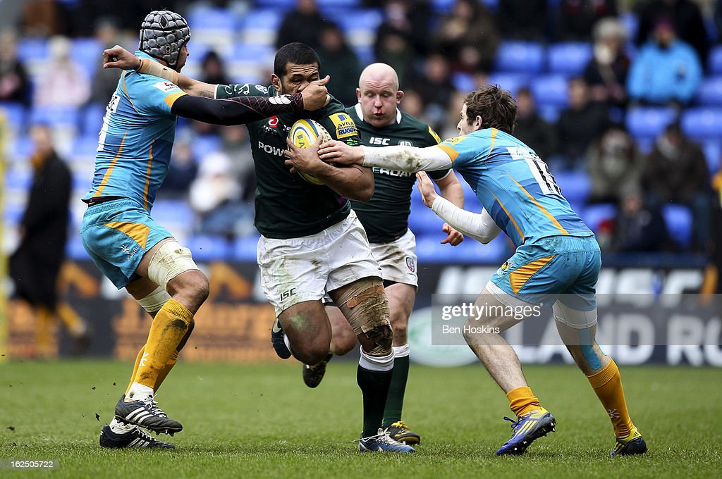 Chris Hala'Ufia of London Irish is tackled by Marco Wentzel (L) and Elliot Daly (R) of Wasps during the Aviva Premiership match between London Irish and London Wasps at the Madejski Stadium on February 24, 2013 in Reading, England.