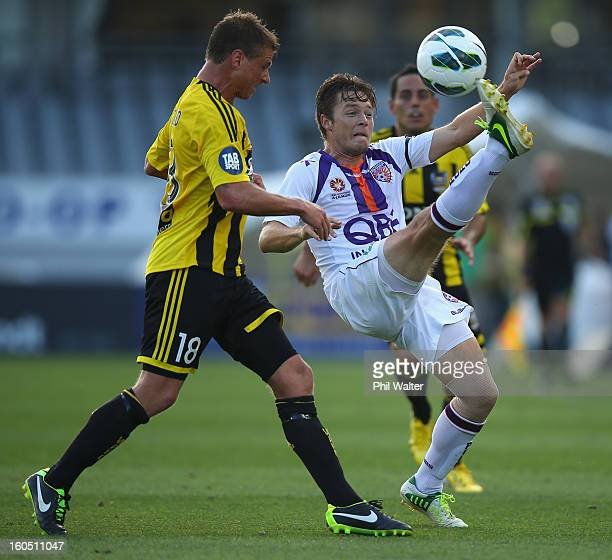 Chris Harold of Perth clears the ball under pressure from Ben Sigmund of the Phoenix during the round 19 ALeague match between the Wellington Phoenix...