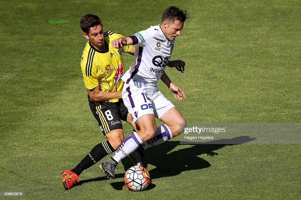 Chris Harold of the Glory goes down in the challenge of Alex Rodriguez of the Phoenix during the round 18 A-League match between Wellington Phoenix and Perth Glory at Westpac Stadium on February 7, 2016 in Wellington, New Zealand.