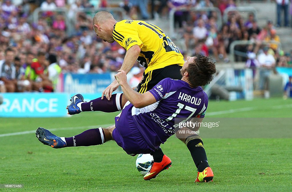 Chris Harold of the Glory is knocked top the ground in a heavy tackle with Stein Huysegems of the Phoenix during the round 25 A-League match between the Perth Glory and the Wellington Phoenix at nib Stadium on March 17, 2013 in Perth, Australia.