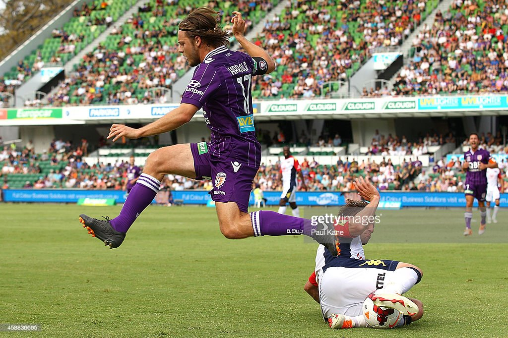 Chris Harold of the Glory jumps over Jeronimo Neumann of Adelaide during the round 11 A-League match between Perth Glory and Adelaide United at nib Stadium on December 22, 2013 in Perth, Australia.