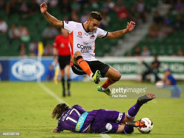 Chris Harold of the Glory slide tackles Jack Hingert of the Roar during the round 15 ALeague match between Perth Glory and the Brisbane Roar at nib...